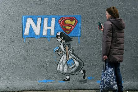 A woman looks at a mural of an NHS worker outside a pub in Pontefract, West Yorkshire. Pic: Jonathan Gawthorpe