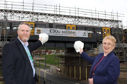 John Fenwick, Nexus' Director of Finance and Resources, and Coun Gladys Hobson, Chair of Tyne and Wear Transport Sub-Committee, raise a hat to the �300million banner.