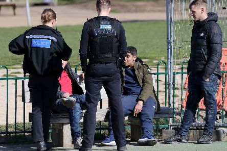 A group of young men are spoken to by Kent Police officers before being dispersed from a children's play area in Mote Park, Maidstone, the day after Prime Minister Boris Johnson put the UK in lockdown to help curb the spread of the coronavirus. PA Photo.