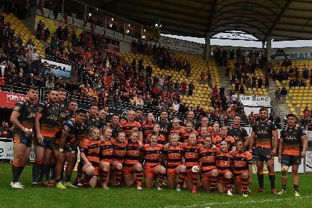 Castleford Tigers Women are pictured with the men's team and the Tigers fans behind them at Catalans' Stade Gilbert Brutus. Picture: Matthew Merrick