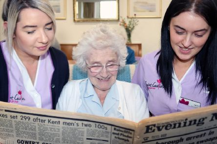 Gloria Walker, a resident at Normanby House, reads the news from July 1985 with care assistants Trudi Hewitt, left and Laura Cambleman.