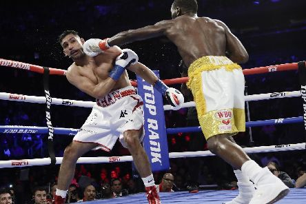 Terence Crawford, right, punches England's Amir Khan during the fifth round of a WBO world welterweight championship boxing match Sunday, April 21, 2019, in New York. Crawford won the fight.