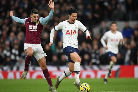 Heung-Min Son of Tottenham Hotspur beats the tackle of Matthew Lowton of Burnley on his way to scoring