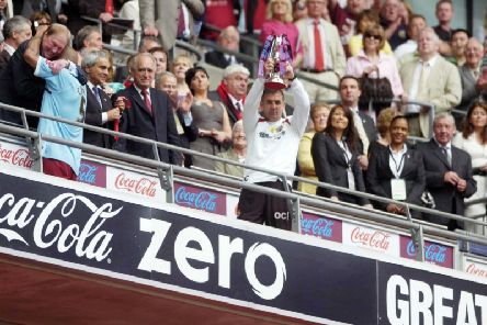 Former Burnley boss Owen Coyle holds the Championship play-off trophy aloft at Wembley a decade ago
