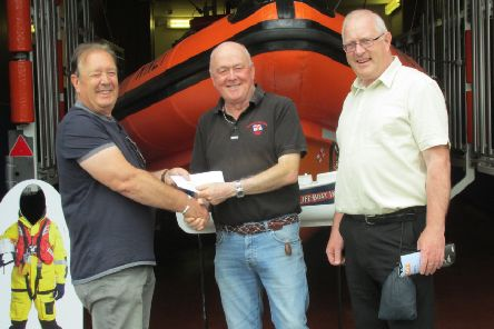 The late Ken Thompson's sons Tony and Alyn hand over the cheque to Paul Hart of the RNLI.