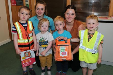 Children from the early years hold the defibrillator with teacher Nikki Skyes and manager Emily Atkins.