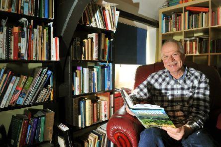 Author Julian Morgan at his home surrounded by books.