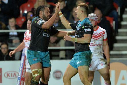 Ash Handley celebrates with Konrad Hurrell after scoring Leeds Rhinos' third try at St Helens.