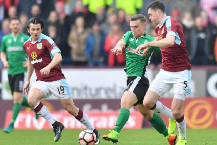 Jack Muldoon runs between England internationals Joey Barton, left, and Michael Keane during Lincoln City's FA Cup win over Burnley at Turf Moor in 2017. Picture: Getty Images