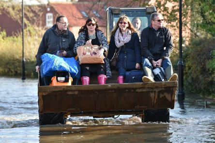A JCB transports people and their belongings through floodwater to other parts of Fishlake, Doncaster. Picture: Ben Birchall/PA Wire