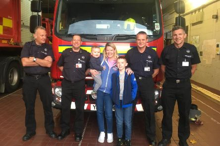 11-year-old Michael Bottomley with mum Leonie Taylor, 2-year-old brother Tommy and the White Watch firefighters