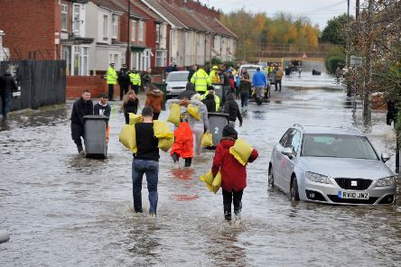Residents using wheelie bins and wheel barrows to sandbag properties on Conyers Road on a flooded estate in Bentley, Doncaster on November 8, 2019.   Picture: Tony Johnson