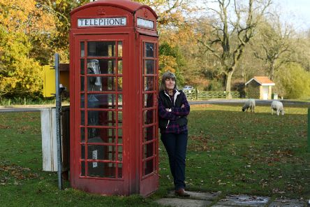 Parish Councillor Jayne Harker with the red phone box on Goathland village green. Picture: Jonathan Gawthorpe