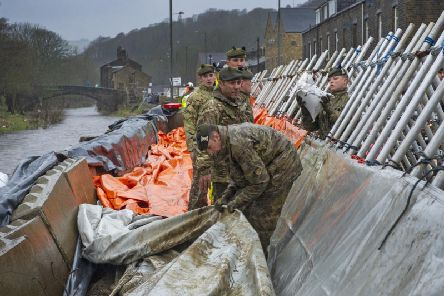 Soldiers from the Highlanders based at Catterick Garrison help build flood defences in Mytholmroyd.