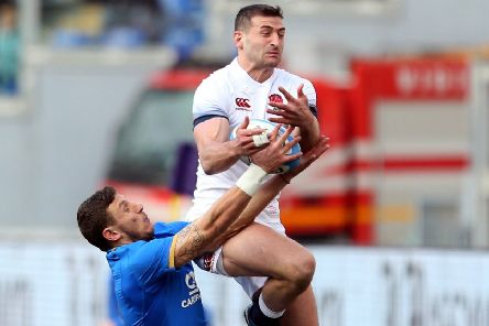 England's Jonny May catches the ball under pressure from Italy's Matteo Minozzi.