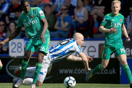 Huddersfiled Town's Aaron Mooy is tackled by Watford's Abdoulaye Doucoure at the John Smith's Stadium. Picture: Clint Hughes/PA
