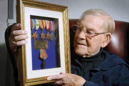 D Day veteran Leslie Harry Postill, from Whinmoor, Leeds looks at some of his military medals. Picture Tony Johnson.