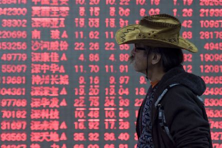 A man walks past an electronic board displaying stock prices at a brokerage house in Hangzhou in east China's Zhejiang province,  (Chinatopix via AP)