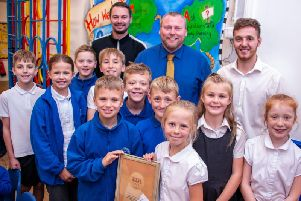 Mapplewells teachers Tom Darby (left), Grant Worthington (head teacher) and Rikki Platts (right) and pupils with the gold award.