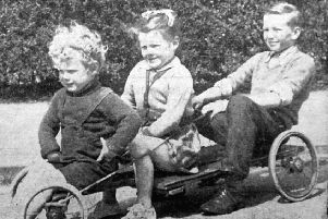 All aboard and ready to go: Three youngsters in the late 1950s enjoy a run on their home-made trolley through the new Chickenley estate. Paul Wilkinsonn aged two at the front with his sister, Linda, aged three, and David Firth, aged 11 at the controls.