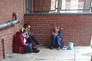 Three people dressed in NHS uniforms - with coats over the top - smoking in an alleyway near to the maternity unit at Blackpool Victoria Hospital