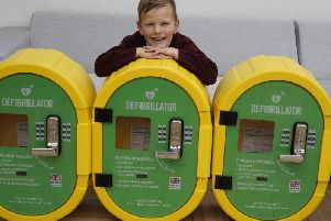 Austin Brennand, five, with the three defibrillators for Ansdell, the first of which has now been installed at the Institute in Woodlands Road