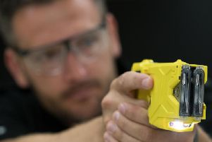A police officer takes aim with a Taser