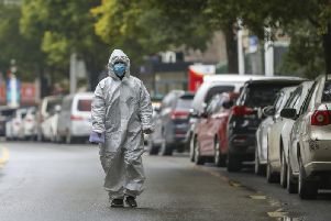 A medical worker in protective gear walks in the street near a community health station in Wuhan in central China's Hubei Province, Monday, Jan. 27, 2020. China on Monday expanded sweeping efforts to contain a viral disease by extending the Lunar New Year holiday to keep the public at home and avoid spreading infection. (Chinatopix via AP)