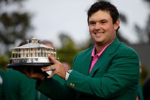 Patrick Reed holds the championship trophy