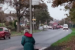 A woman waits for a bus on busy Poulton Road, where residents say elderly people are struggling to reach the post office, which is based inside the garage