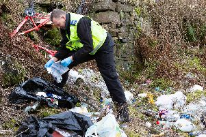 Community Safety Warden inspects rubbish at a fly tipping hot spot in Pellon,