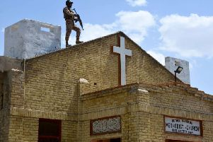 A soldier stands guard on the roof of a Methodist Church.