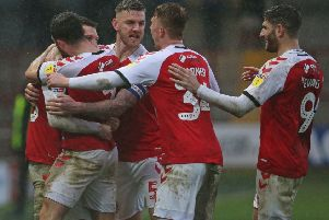 Fleetwood Town's James Husband (left) is swamped by team-mates as he celebrates scoring against Gillingham in March