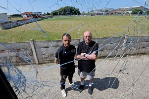 Club welfare officer Justin Singleton with club secretary Billy Singleton, pictured through a window which was smashed by vandals