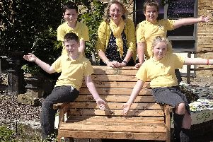 Wheatcroft School headteacher Jenny Hartley with pupils Seth, Ethan, Emily and Freya at the memorial bench dedicated to the memory of Nick Earnshaw in their special garden. Picture by Richard Ponter