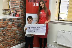 Owen Brown is pictured handing over a cheque to Lucinda Bury from the hospice
