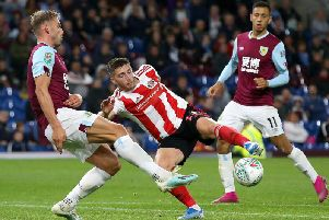 Burnley's Charlie Taylor closes down Sunderland's Lynden Gooch during the Carabao Cup tie at Turf Moor as Dwight McNeil looks on