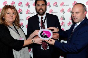 Neil Hart, chief executive of Burnley FC in the Community (centre), along with Matt Hargreaves, Leisure Box general manager receive their award.