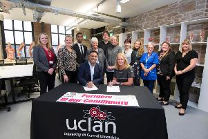 Dr Ebrahim Adia, pro vice-chancellor (Business Development and Partnerships), and Helen McVey, chief executive of Pendleside Hospice, signing the Memorandum of Understanding watched by staff members from UCLan Burnley and Pendleside.