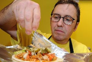 Richard Golland, of Street Food Chef, inside their third shop on Glossop Road, sprinkles cheese onto a taco. Picture: Andrew Roe
