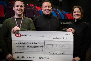 Aiden Kelly (left) who is finance and operations co-ordinator at Burnley Youth Theatre receives the cheque from Mark Dempsey who is Hospitality General Manager for Burnley Leisure and Krista Humphreys who is the assistant hospitality manager.