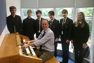 Robin Forbes, King Edward VI School head of music, and a group of students are pictured with the electronic organ.