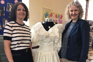 Mount Zion Church treasurer Helen Keegan with her wedding dress she wore when  when she tied the knot at the church. She is pictured with one of her bridesmaids.