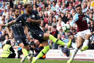 Burnley's Dwight McNeil crosses despite the attentions of Manchester City's Kyle Walker