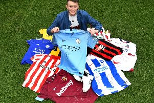 Ellis Lee with a selection of the signed shirts he's been donated