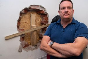 Lee Bradshaw next to one of the walls that raiders drilled through at Burnley Auctioneers.