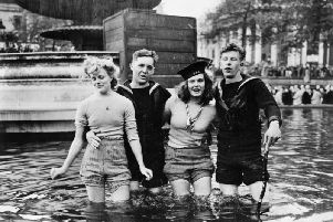 Two Royal Navy personnel celebrate with two young ladies on VE Day in London's Trafalgar Square