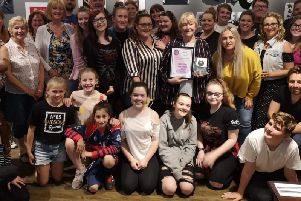 Hazel Hodder, honorary president of Burnley Panto Society, holding the Most Accomplished Panto, alongside cast and crew.