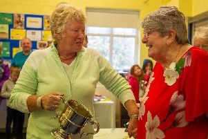Catherine Briggs (left) receives one of her many trophies from Marie Heys  at Cliviger Flower Show.