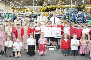 James Woodhouse, (behind the centre of the cheque) with his classmates from Clayton-le-Woods Primary School at Leyland Trucks'Behind him is Stuart Derbyshire (Cycle Ride Organiser) and Matt Kersey (Helping Hand Chairman)
